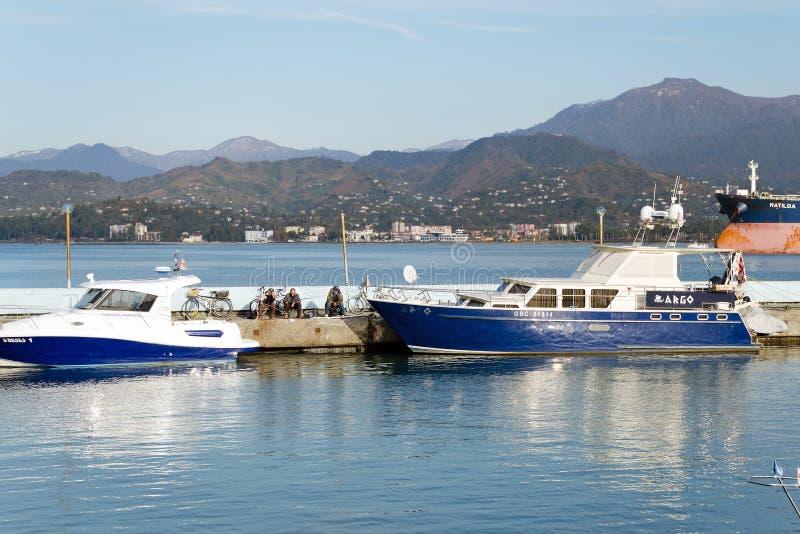 Port på bakgrunden av berg - parkerade fartyg, ett nöjefartyg, en släp Fiskare fiskar arkivbilder