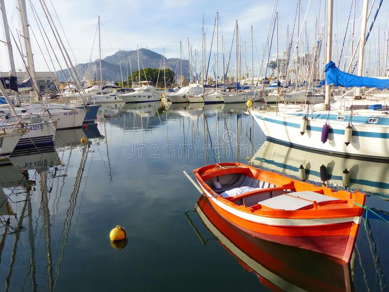 Port of palermo with in the foreground an orange boat. Palermo. Sicily, Italy. Mountains in distance. Travel destination. Blue sky with white clouds. Sunny day stock images