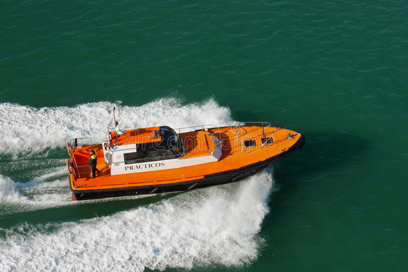 Port pilot on small vessel moving at high speed. Small orange boat shipping on sea water. Pilot boat for guidance into harbor.Equi royalty free stock photos