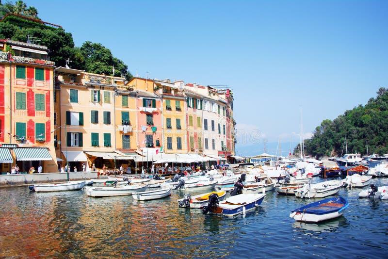 Port Portofino, Italien, Genova, Liguria, 09 augusti, 18: Gå turister, hemtrevliga kaféer, kulöra hus, boatsin den pittoreska ham royaltyfri foto
