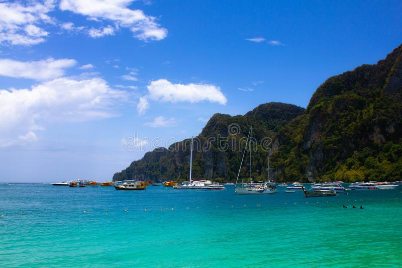 Port with sailboats in a lagoon with clear blue sea water on a background of wild rocks in Thailand. Turquoise sea, blue sky and stock photography
