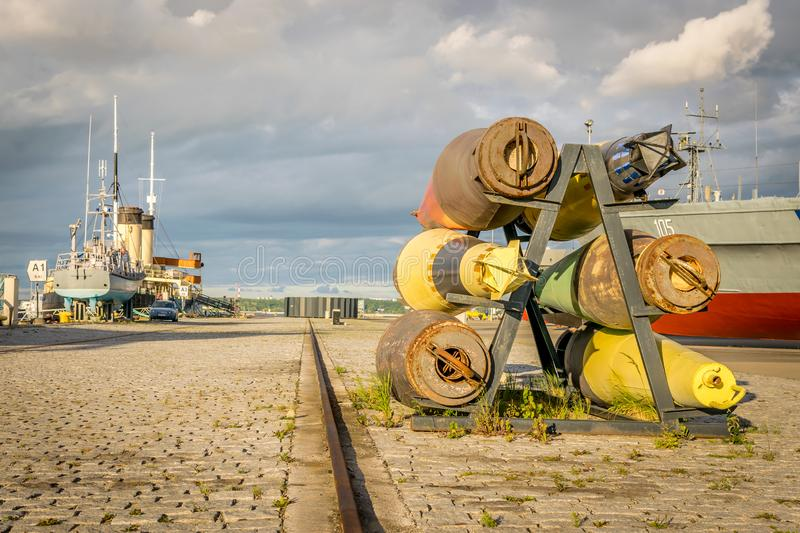 A port with ships and old military bombs. A port or harbour with ships and boats. old rusty military bombs and torpedoes. gathering fluffy clouds royalty free stock photos