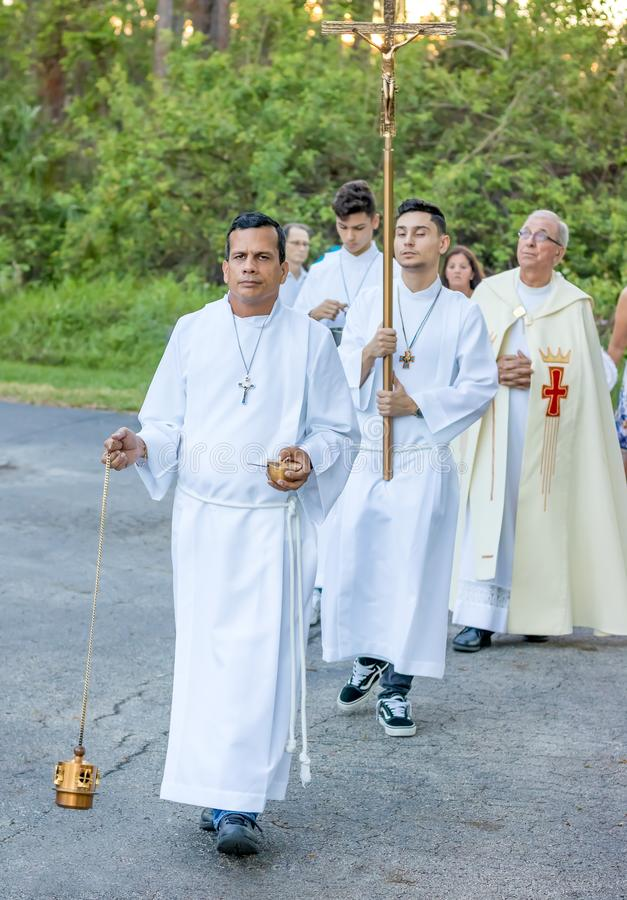 Altar boy leads an outdoor catholic procession royalty free stock photos