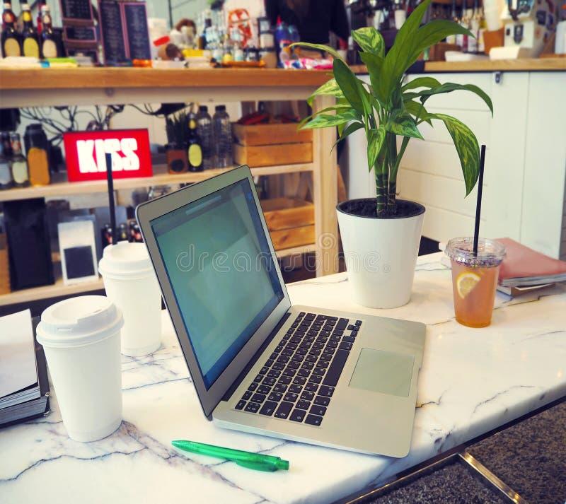 Port?til com a tela branca vazia na tabela de m?rmore no caf? moderno fotografia de stock