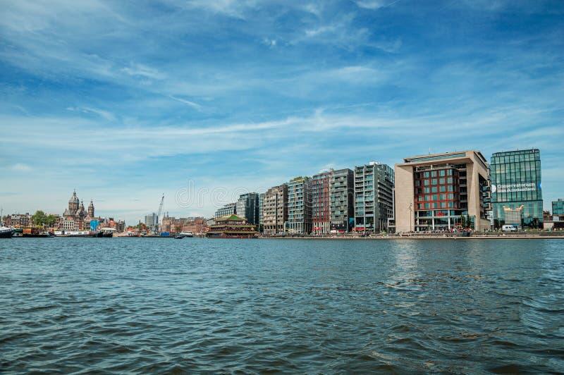 Port, torri di chiesa e costruzioni moderne sulla banca e sul cielo blu del canale a Amsterdam immagini stock libere da diritti