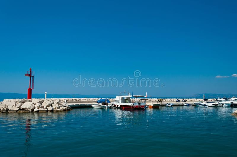 Port of Tucepi with ships and lighthouse. Croatia stock image