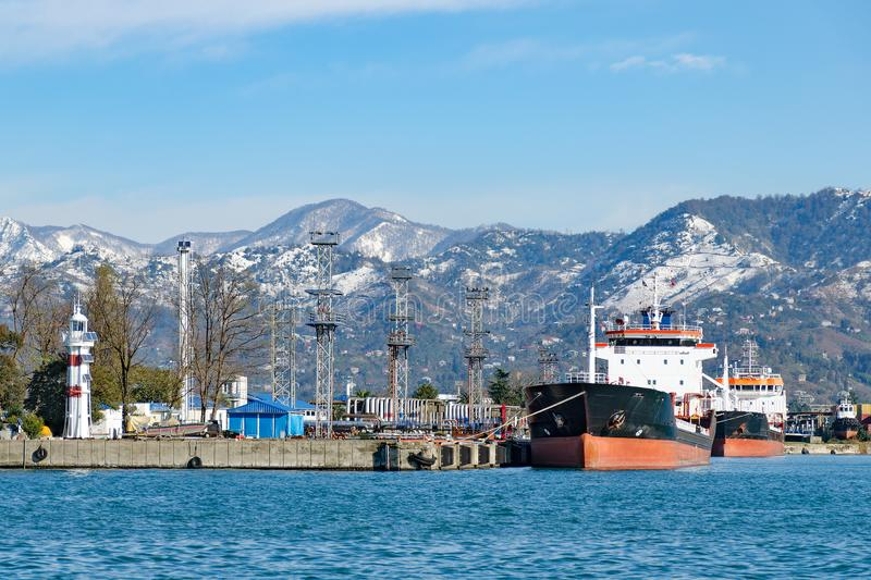 Port view - ships in the harbor, a lighthouse, snowy mountains in the background royalty free stock photos