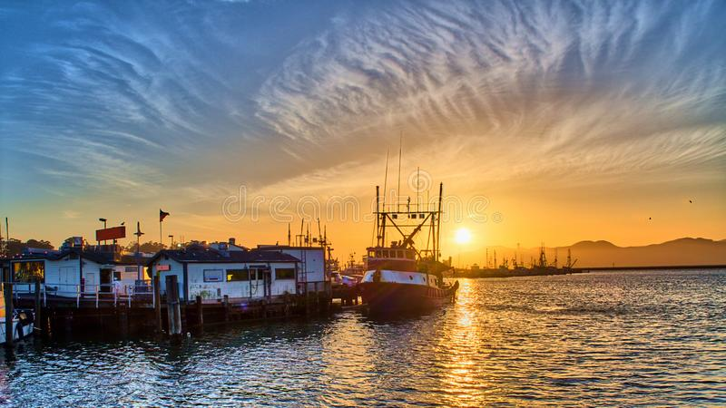Port view at sunset from San Francisco Fisherman`s Wharf. With a shpi and docks at the front stock images