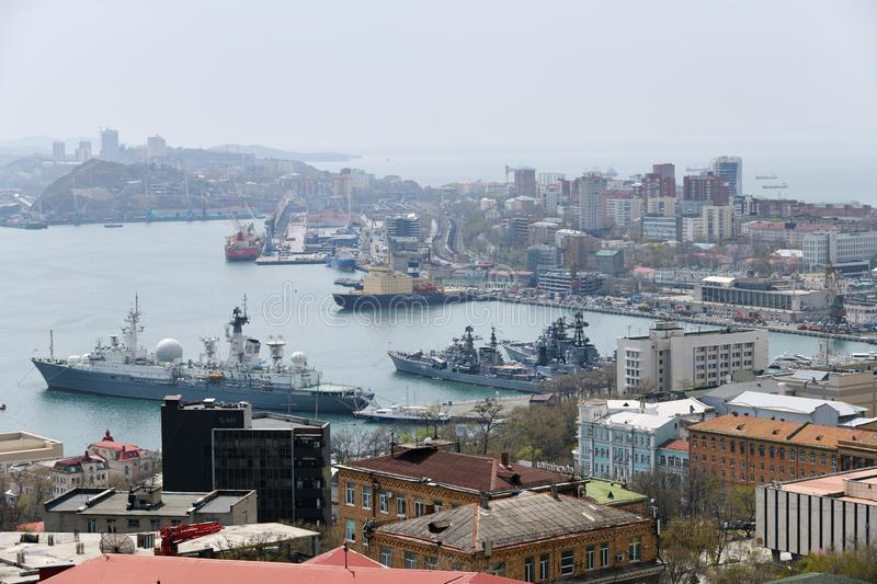 Port Vladivostok, Russia. Skyline and Pacific navy fleet and commercial vessels. Vladivostok, Russia - April 28, 2019: City skyline, Golden Horn Bay, commercial royalty free stock photography