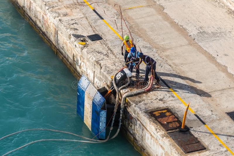Port workers on mooring rope in Barbados royalty free stock image