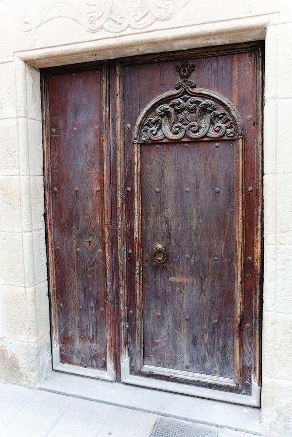 A porta é feita da madeira velha com as decorações interessantes da porta em Catalonia, Espanha imagem de stock