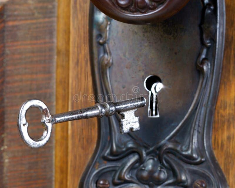 Porta antiga com a chave de esqueleto que entra no furo chave imagem de stock