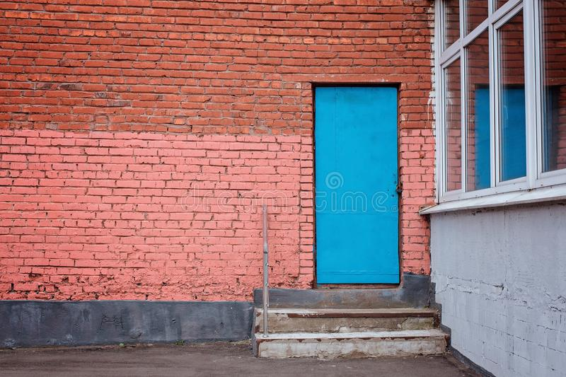 Porta azul com etapas na parede de tijolo imagens de stock royalty free