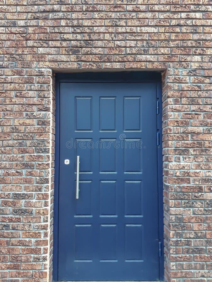 Porta azul do metal em uma parede de tijolo vermelho fotos de stock royalty free