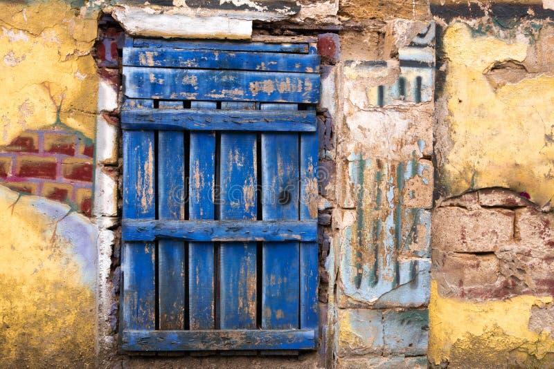 Porta azul velha contra uma parede amarela fotos de stock