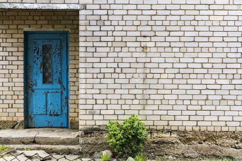 Porta azul velha em uma parede de tijolo branca imagem de stock