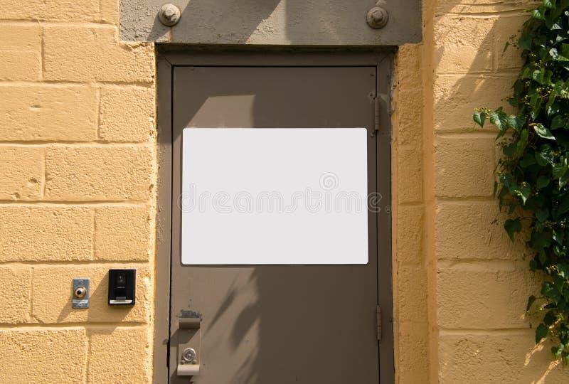 Porta beige del metallo in parete gialla del blocchetto di cenere con il segno in bianco bianco immagini stock