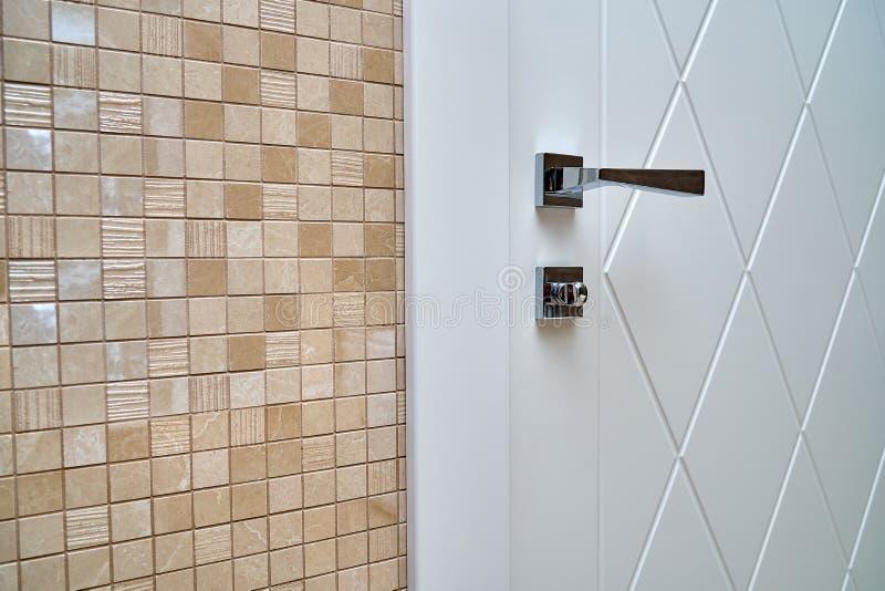 Porta bianca contemporanea con la maniglia brillante in bagno fotografia stock