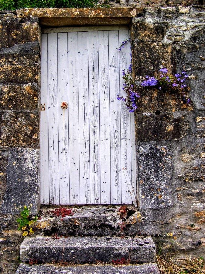 Porta bianca in un vecchio villaggio rurale del vicolo in Francia Europa con i fiori fotografie stock libere da diritti