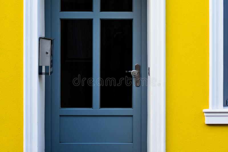 Porta blu in una casa gialla immagini stock libere da diritti