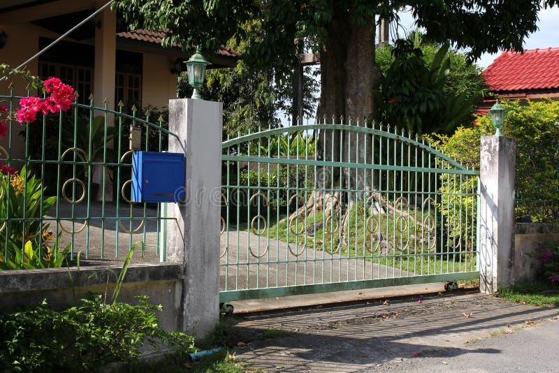 Porta bonita da entrada do metal Jardim verde e dia ensolarado fotografia de stock