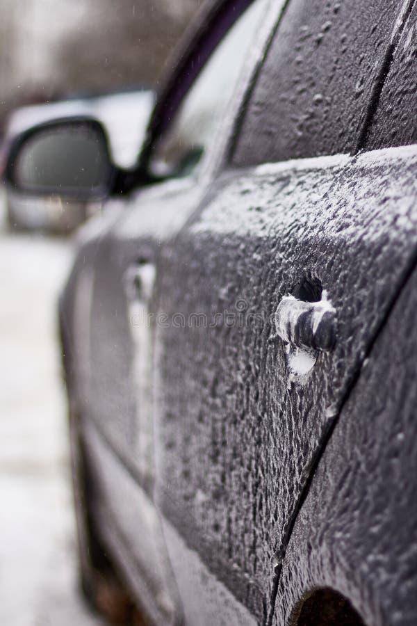 Porta, botão, buraco da fechadura do carro coberto com a neve e gelo após uma queda de neve fotos de stock