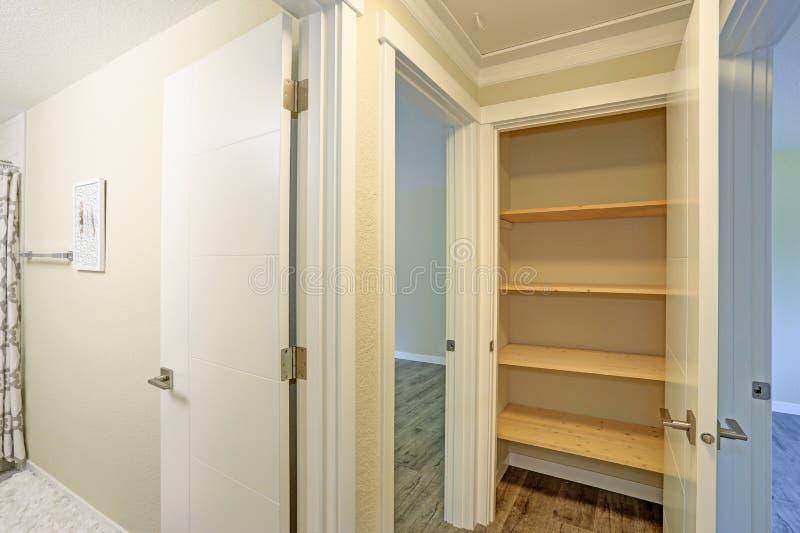 A porta branca abre a uma despensa da cozinha enchida com as prateleiras de madeira imagens de stock