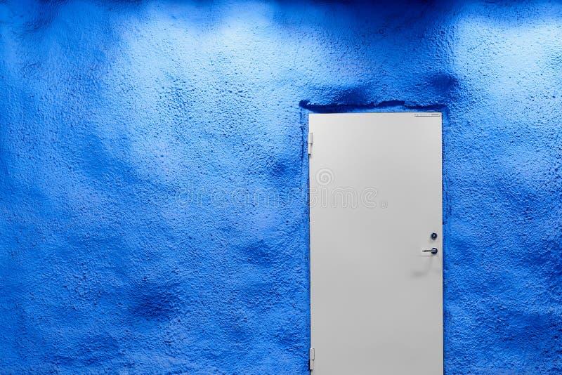 Porta branca e parede azul com sombras e luz fotografia de stock