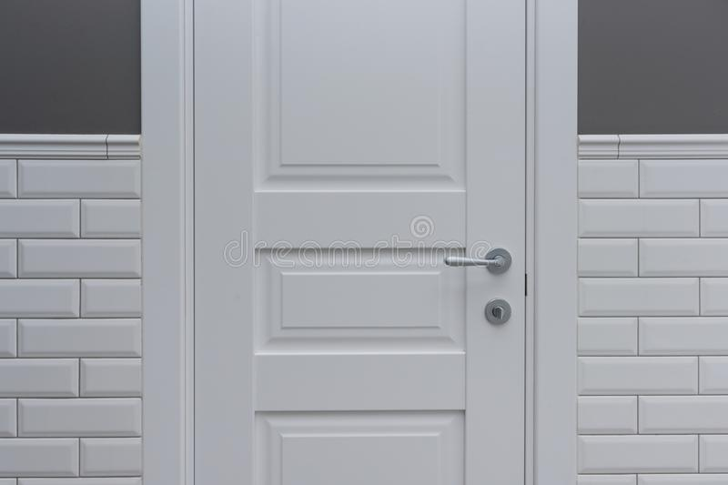 Porta branca na sala do toalete do banheiro O cinza do fundo pintou a parede coberta com os azulejos decorativos com o tijolo lus foto de stock
