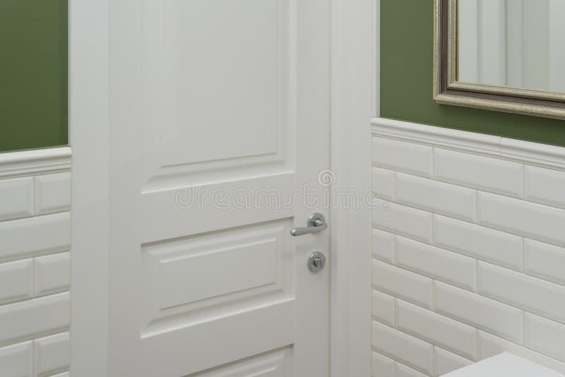 Porta branca na sala do toalete do banheiro O verde do fundo pintou a parede coberta com os azulejos decorativos com o bric lustr fotos de stock royalty free