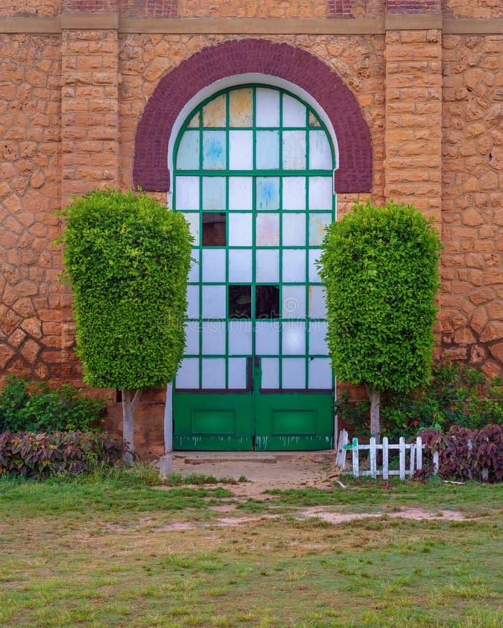 Porta chiusa di lerciume con la griglia verde del metallo incorniciata da due cespugli verdi in parete di pietra dei mattoni aran fotografia stock libera da diritti