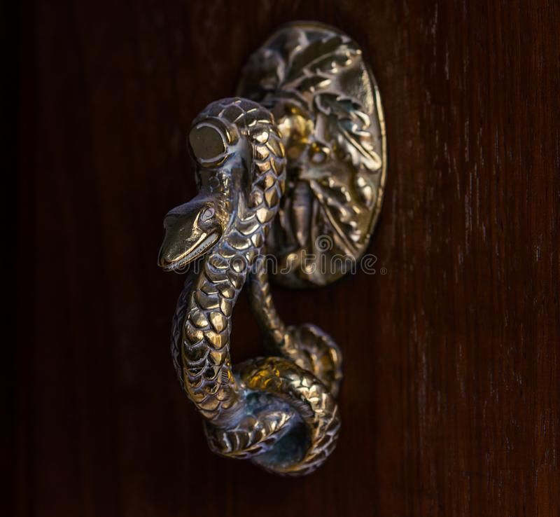 Porta com a aldrava de bronze na forma de uma serpente, entr bonito fotografia de stock
