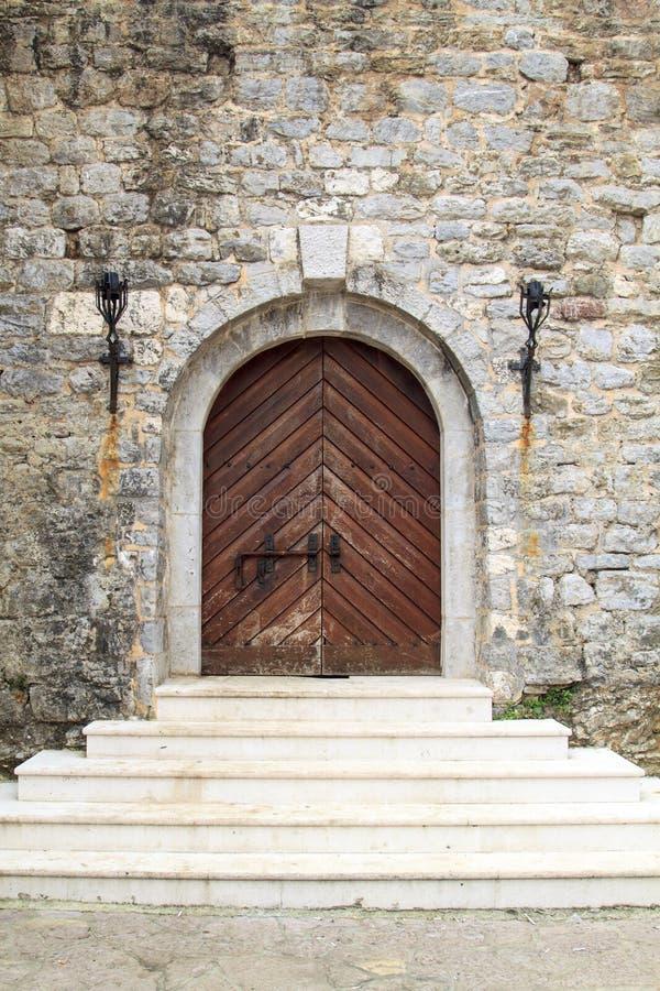 porta com etapas do castelo com a parede de pedra na cidade velha de Budva, segunda-feira foto de stock