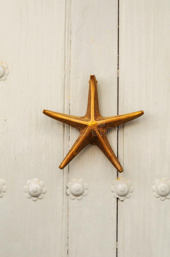 Porta con il battitore d'ottone sotto forma di una stella marina, bella en fotografia stock