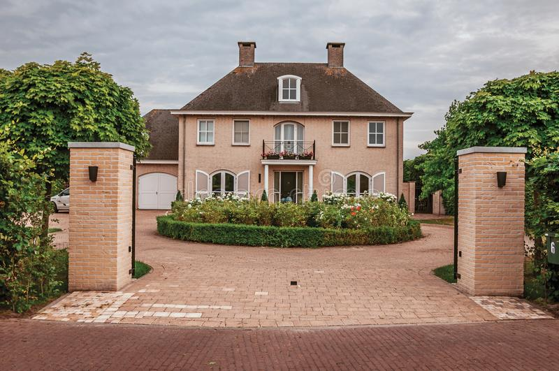 Porta da entrada aberta ao jardim do pátio na casa elegante do tijolo em um dia nebuloso em Drimmelen fotografia de stock