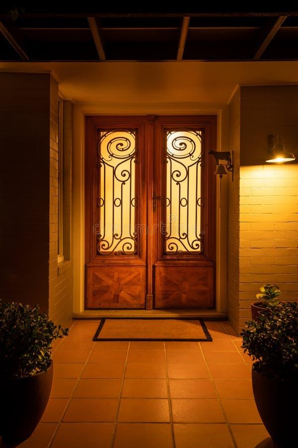 Porta da rua à casa suburbana doméstica iluminada na noite do interior e abaixo das luzes de fora foto de stock royalty free