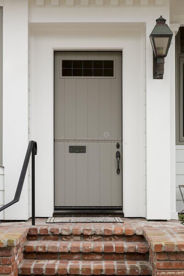 Porta da rua com o branco exterior e uma grande luz do patamar com escadaria do tijolo imagens de stock