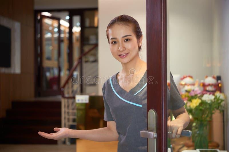 Porta de abertura asiática do trabalhador do salão de beleza para convidados foto de stock royalty free