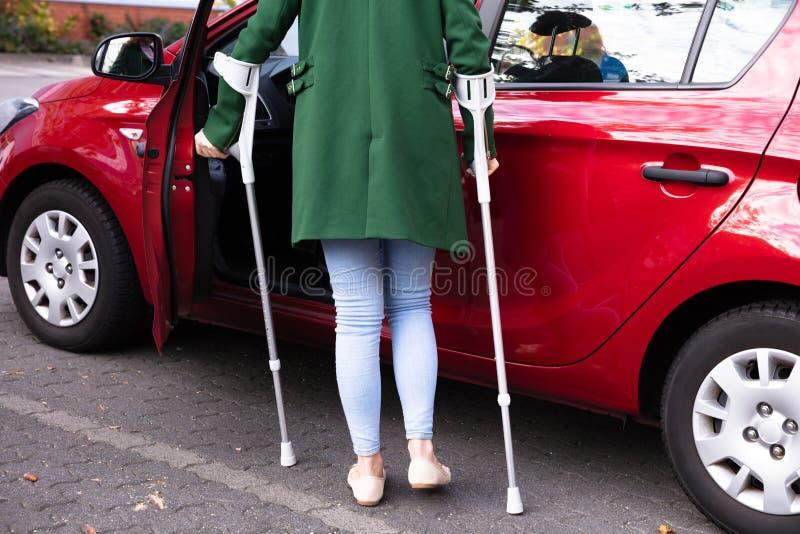 Porta de abertura da mulher deficiente de um carro imagem de stock