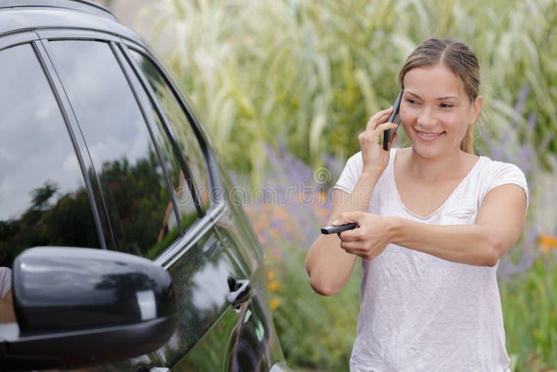 Porta de carro da abertura da mulher ao usar o telefone imagens de stock royalty free