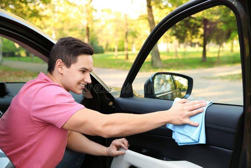 Porta de carro da lavagem do homem novo com pano imagens de stock royalty free
