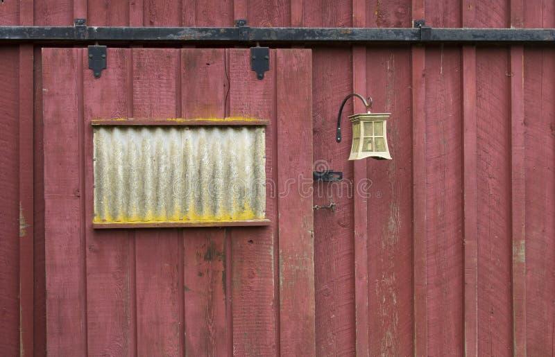 Porta de celeiro vermelha resistida com dispositivo bonde claro foto de stock royalty free