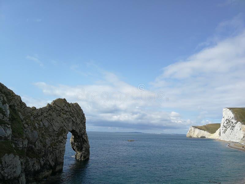 Porta de Durdle em Dorset, Inglaterra - mares calmos e céu azul fotos de stock royalty free