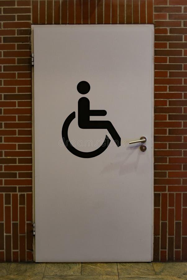 Porta de entrada ao toalete público para deficientes motores Sinal do toalete na porta imagens de stock royalty free