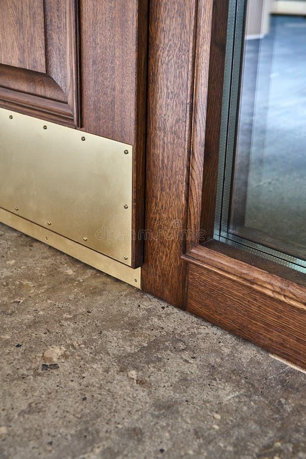 Porta de entrada da madeira maciça com as placas de pontapé de bronze contínuas Porta de entrada com luz lateral Processo de manu foto de stock