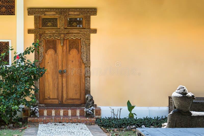 Porta de entrada de madeira com testes padrões cinzelados nela Parede amarela vazia com espaço para uma inscrição imagens de stock royalty free