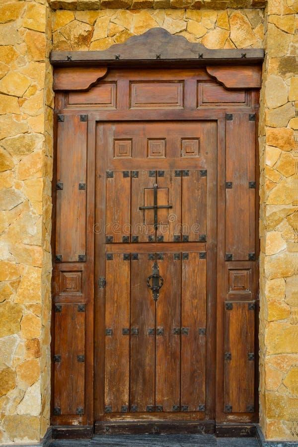 A porta de entrada de madeira resistida da prancha da casa de campo residencial da mansão da casa com ferro forjado articula trav fotografia de stock