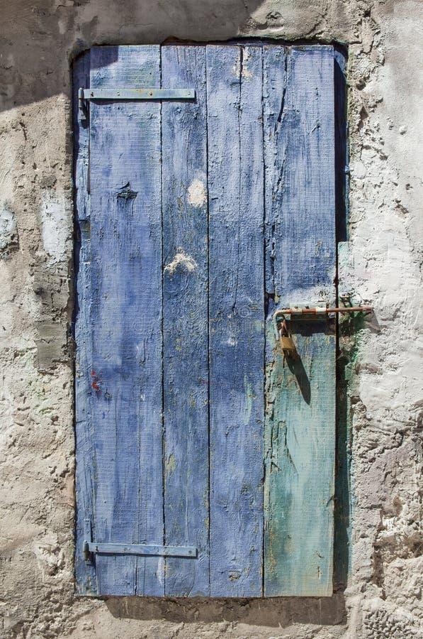 A porta de madeira áspera aparafusada e fechado pintou o azul foto de stock