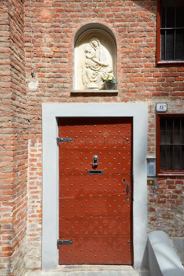 Porta de madeira antiga com relevo dos pregos e de bas da Virgem Maria em um dia ensolarado em Mondovi, Itália fotografia de stock