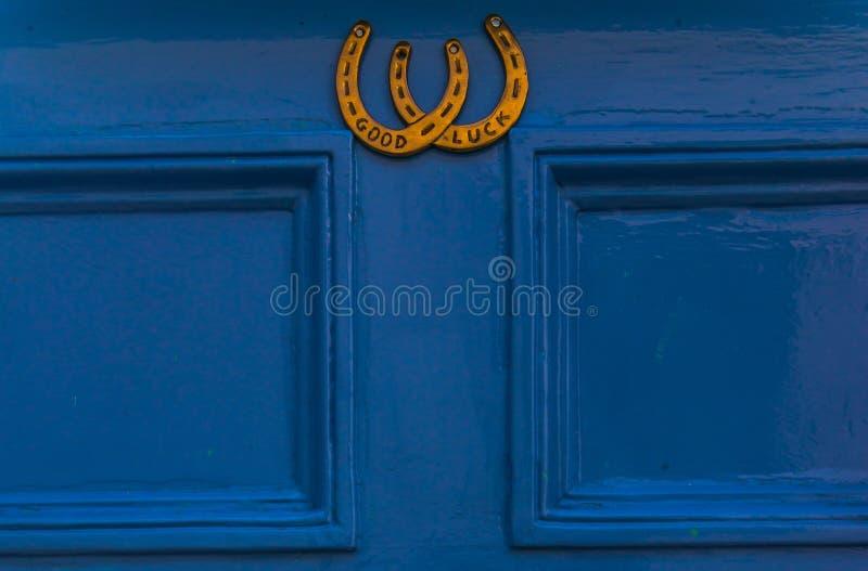 Porta de madeira azul a abrigar com uma aldrava de bronze na forma de h fotos de stock